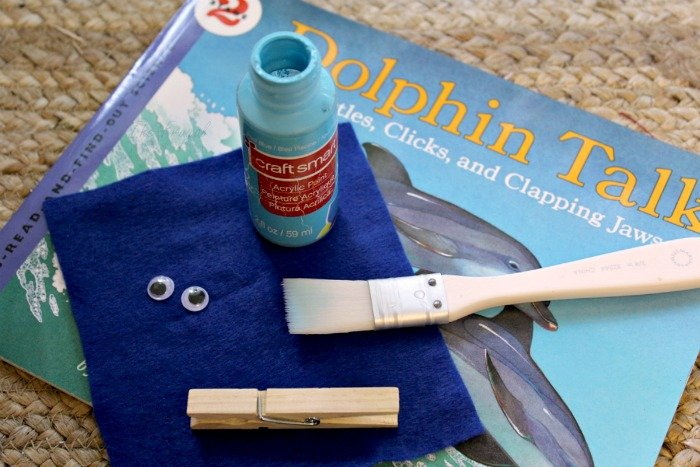 Items for clothes pin craft. Dolpin Talk Science book, blue paint, blue felt, googly eyes, paint brush, and clothes pin.