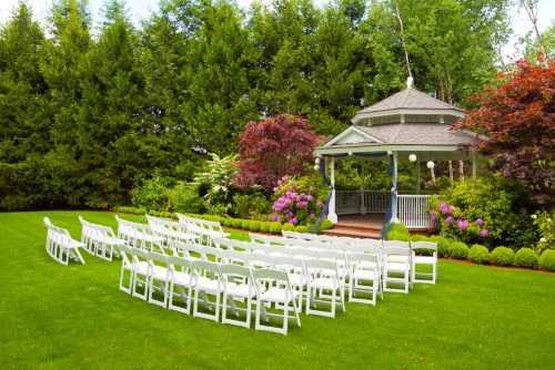 A gazebo and white chairs at a wedding venue for the ceremony and reception.
