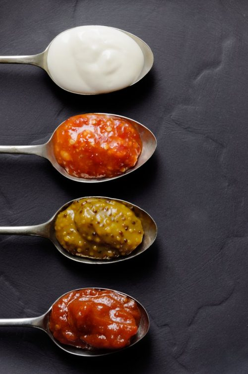 Different sauces and jams on spoons